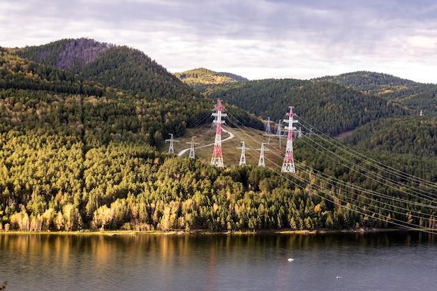 Słupy linii wysokiego napięcia w górach na brzegu rzeki produkcja i przesył energii elektrycznej