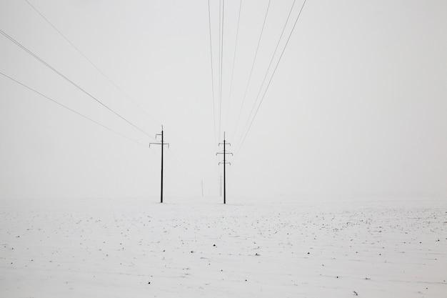 Słupy z liniami elektrycznymi w sezonie zimowym. pochmurna pogoda z białym niebem i białym śniegiem na ziemi. krajobraz