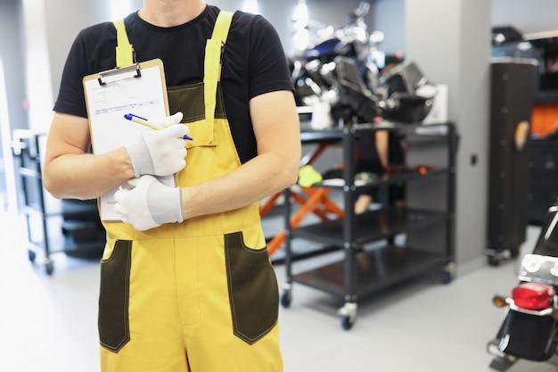 Ślusarz mechanik samochodowy w żółtym mundurze stoi w warsztacie samochodowym i serwisie motocyklowym