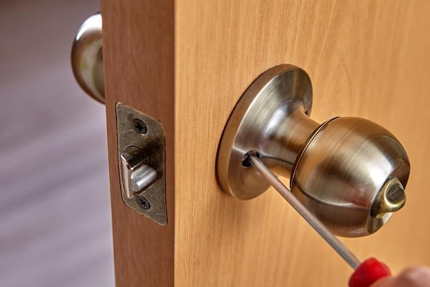 Ślusarz mocuje klamkę za pomocą śrubokręta