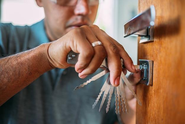 Ślusarz otwierający drzwi naprawa męskich rąk lub montaż metalowego zamka drzwi za pomocą śrubokręta