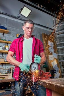 Ślusarz tnie metal szlifierką, piła mechaniczna piła mechaniczna.