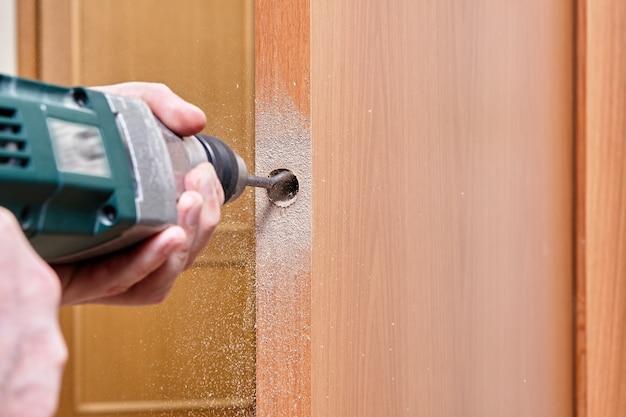 Ślusarz używa płaskiego wiertła do drewna podczas wiercenia otworu na zatrzask.