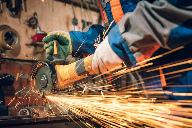 Ślusarz w specjalnej odzieży i goglach pracuje przy produkcji. obróbka metalu szlifierką kątową. iskry przy obróbce metali.