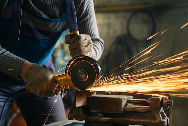 Ślusarz w specjalnej odzieży i goglach pracuje przy produkcji. obróbka metalu szlifierką kątową