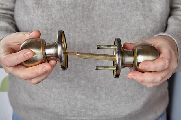 Ślusarz wkłada trzpień do klamki drzwi wewnętrznych, aby sprawdzić działanie mechanizmu zamka.