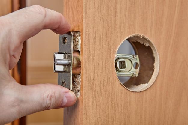 Ślusarz wpycha zapadkę wraz z montażem przez otwór krawędziowy drzwi wewnętrznych drewnianych podczas montażu zamka z klamką.