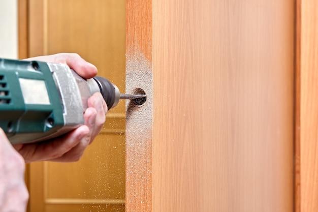 Ślusarz z elektrycznym wierceniem otworu na zatrzask drzwi
