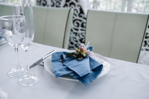 Służy do weselnego stołu bankietowego w niebiesko białym kolorze. dekoracja ślubna. błękitna pielucha z kwiatem na białym talerzu.