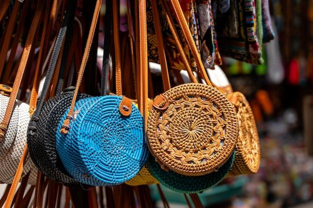 Słynne balijskie ekologiczne torby rattanowe na lokalnym targu z pamiątkami na ulicy w ubud, bali, indonezja. wystawa rękodzieła i sklepu z pamiątkami, z bliska
