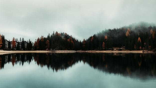 Słynne jezioro lago di braies we włoszech przy mglistej pogodzie z pięknymi odbiciami w sezonie jesiennym