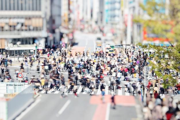 Słynne przejście dla pieszych shibuya w tokio, japonia, z spacerującymi ludźmi