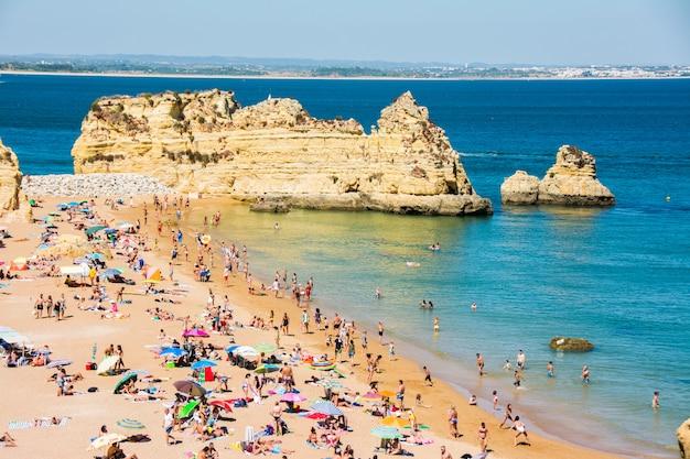 Słynne skały w morzu, oceanie, lagos w portugalii. plaża i kąpiący się na wybrzeżu algarve