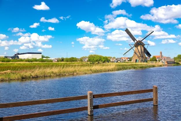 Słynne wiatraki w wiosce kinderdijk w holandii. kolorowy wiosenny wiejski krajobraz z wiatrakiem i rzeką. światowe dziedzictwo unesco i słynna atrakcja turystyczna.