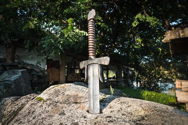 Słynny excalibur miecza króla artura wbity w skałę. broń ostra od legendarnego króla pro artura.