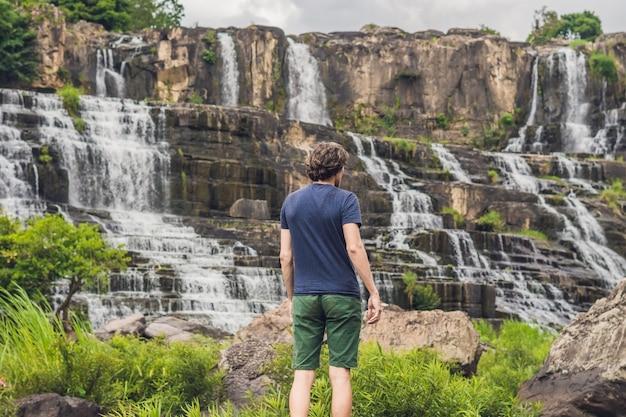 Słynny jest turysta turystyczny mężczyzna na tle niesamowitego wodospadu pongour