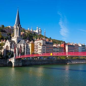 Słynny widok na miasto lyon z czerwoną kładką na saonie i kościołem