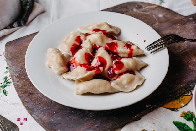 Słynny wschodni posiłek z dushpere z ciastem w środku mielone mięso solone posypane białym talerzem z czerwonym sosem