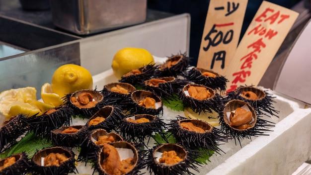 Słynny złoty jeżowiec otwarty i gotowy do jedzenia na lodzie na targu rybnym w kioto. świeże owoce morza uni z oceanu spokojnego to popularne danie japonii. najlepsze z tradycyjnej japońskiej ulicy z jedzeniem.