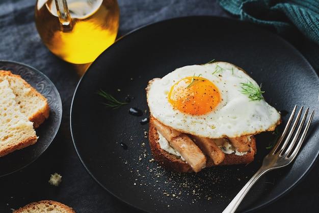 Smaczna apetyczna kanapka z kawałkami kurczaka i jajkiem sadzonym podana na talerzu na ciemnej powierzchni