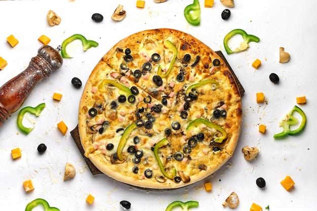 Smaczna, apetyczna klasyczna włoska tradycyjna pizza z serem, oliwkami, świeżymi warzywami i szynką