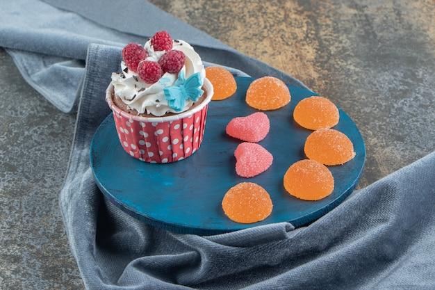 Smaczna babeczka ozdobiona kremem i cukierkami na niebieskiej desce