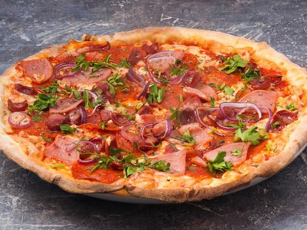Smaczna bawarska pizza z szynką, salami, wędzoną kiełbasą