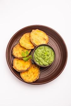 Smaczna brinjal pakora czyli chrupiące placki z bakłażana, indyjska przekąska na podwieczorek podawana z zielonym chutney