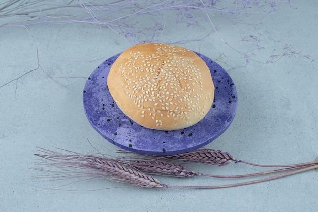 Smaczna bułka burger z sezamem na niebieskim talerzu