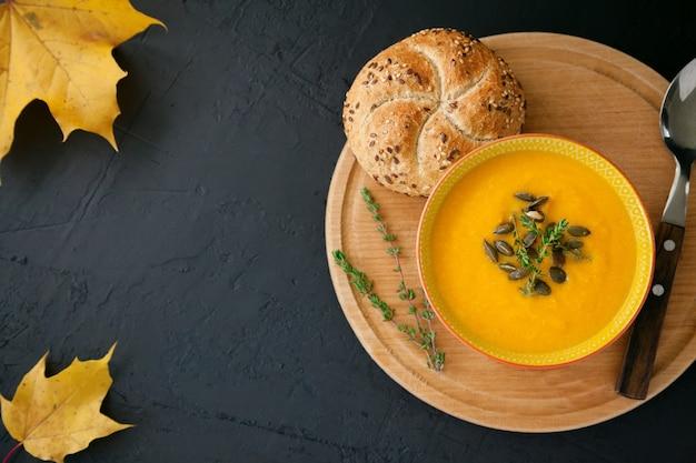 Smaczna domowa zupa dyniowa z serem, podawana z pestkami, ziołami i bułką, na czarnym tle