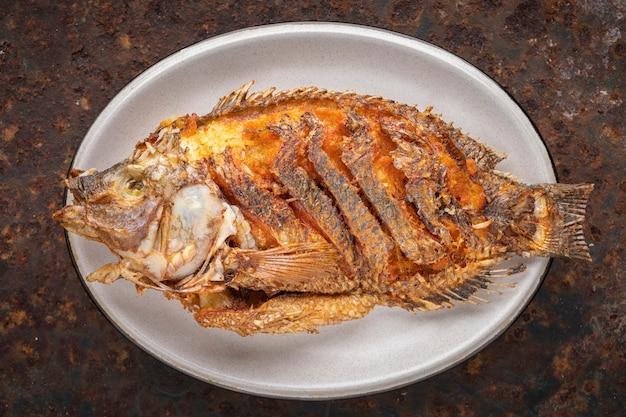 Smaczna duża smażona ryba tilapia nilowa w owalnym talerzu ceramicznym na zardzewiałym tle tekstury, widok z góry