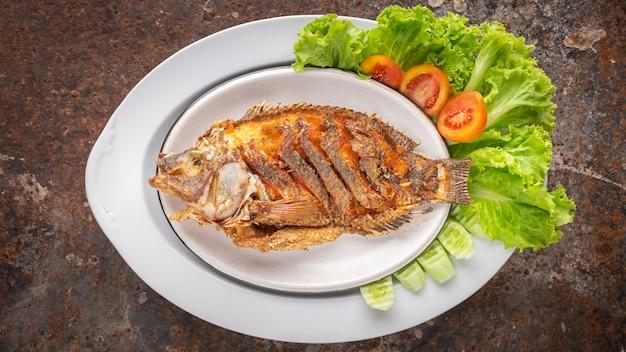 Smaczna duża smażona ryba tilapia nilowa z sałatą, pomidorem i ogórkiem w płycie ceramicznej na zardzewiałym tle tekstury, widok z góry