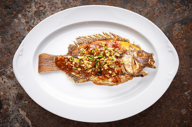 Smaczna duża smażona ryba tilapia nilowa z sosem chlli, smażonym czosnkiem i pokrojoną w plasterki szczypiorkiem w owalnym talerzu ceramicznym na zardzewiałym tle tekstury, widok z góry