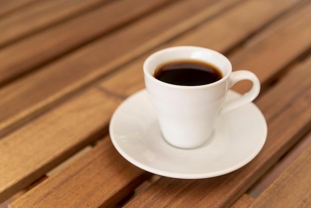 Smaczna filiżanka czarnej kawy na drewnianym stole
