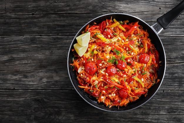 Smaczna gorąca sałatka z dyni z pomidorami, słodką papryką, cebulą, sezamem i orzeszkami pinii