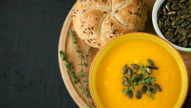 Smaczna gorąca wegańska domowa zupa dyniowa z pestkami, ziołami i bułką na czarnym tle
