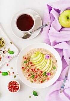 Smaczna i zdrowa owsianka z jabłkami, granatem i orzechami. zdrowe śniadanie. jedzenie fitness. odpowiednie odżywianie. widok z góry