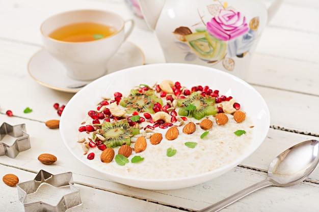 Smaczna i zdrowa owsianka z kiwi, granatem i nasionami. zdrowe śniadanie. jedzenie fitness. odpowiednie odżywianie.