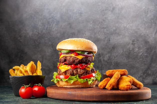 Smaczna kanapka i nuggetsy z kurczaka na brązowej drewnianej desce do krojenia frytki na ciemnej powierzchni lodu