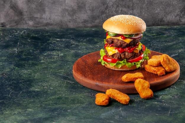 Smaczna kanapka i nuggetsy z kurczaka na brązowej drewnianej desce do krojenia po lewej stronie na lodowej powierzchni z wolną przestrzenią