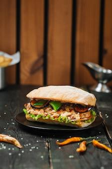 Smaczna kanapka na ciemnym drewnianym stole