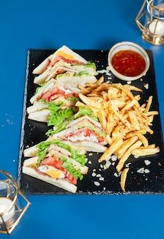 Smaczna kanapka na czarnym kamieniu w eleganckiej restauracji. kuchnia sosowa