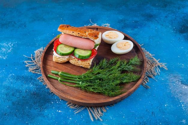 Smaczna kanapka z kiełbasami i koperkiem na drewnianym talerzu.