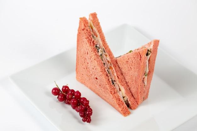 Smaczna kanapka z różowym chlebem na białym talerzu