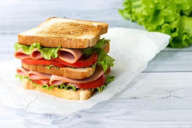 Smaczna kanapka z sałatką z szynki i pomidorami na jasnej powierzchni