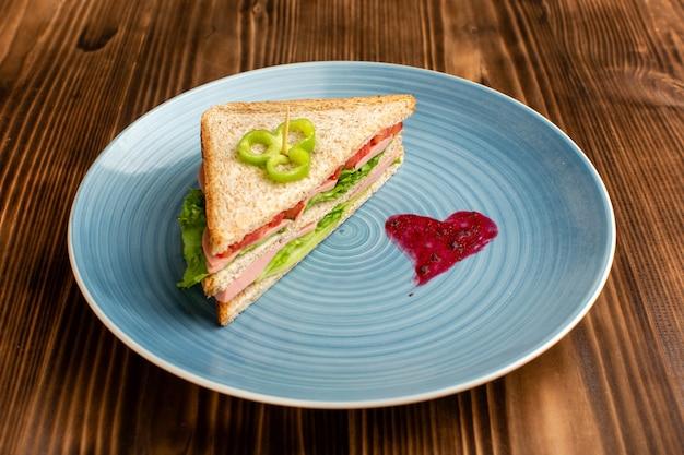 Smaczna kanapka z zielonymi pomidorami sałatkowymi wewnątrz niebieskiej tablicy na brązowym