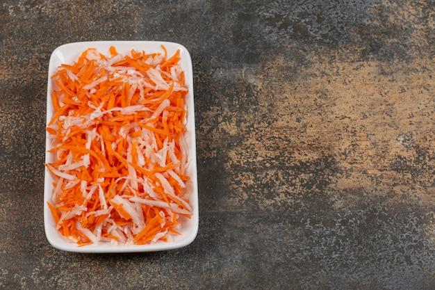 Smaczna kapusta julienned i marchewki na białym talerzu.