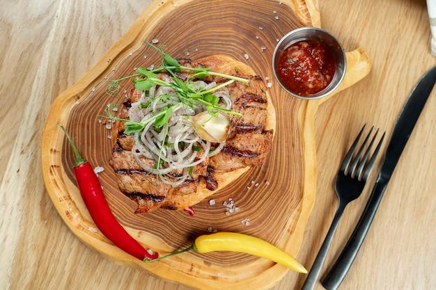 Smaczna karkówka z grilla podana z chlebem pita z cebulą, mikrogranicą i ostrą papryką. drewniany mur. skopiuj miejsce selektywne ustawianie ostrości