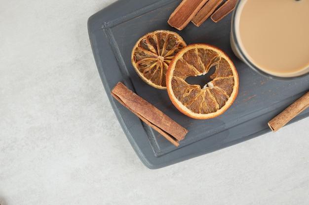 Smaczna kawa, laski cynamonu i plasterki pomarańczy na ciemnym talerzu.