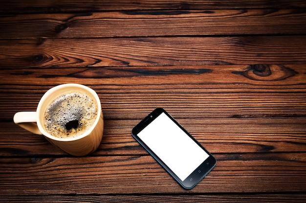 Smaczna kawa z telefonem na drewnianym stole